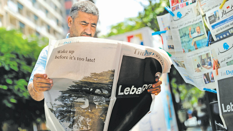 """A man checks a copy of the Lebanese local English-language newspaper  """"The Daily Star"""" in the capital Beirut on Thursday, which refrained from publishing news articles in its print edition in protest against the  """"deteriorating situation"""" in Lebanon. - AFP"""