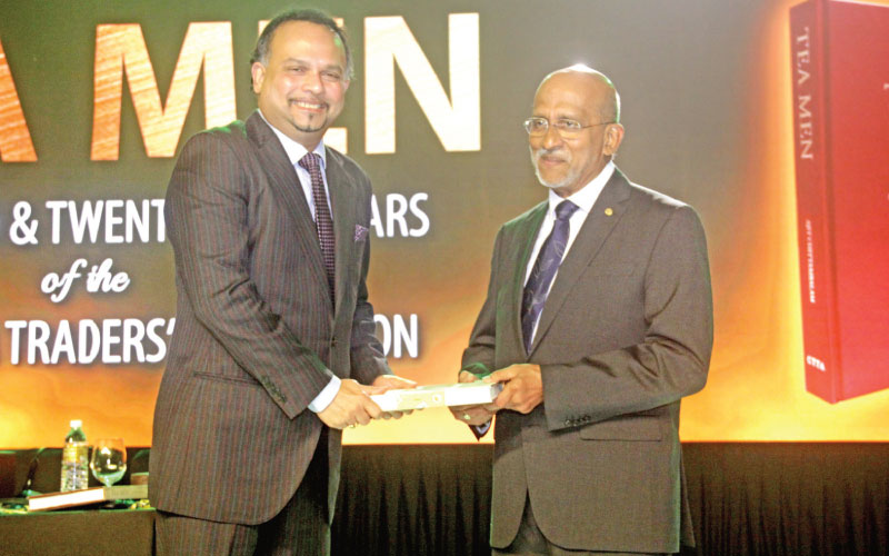 Chairman CTTA Anselm Perera, hands over the anniversary publication 'Tea Men' to Minister Dissanayake at the Shangri-La Hotel in Colombo on Friday. Picture by Chaminda Niroshan