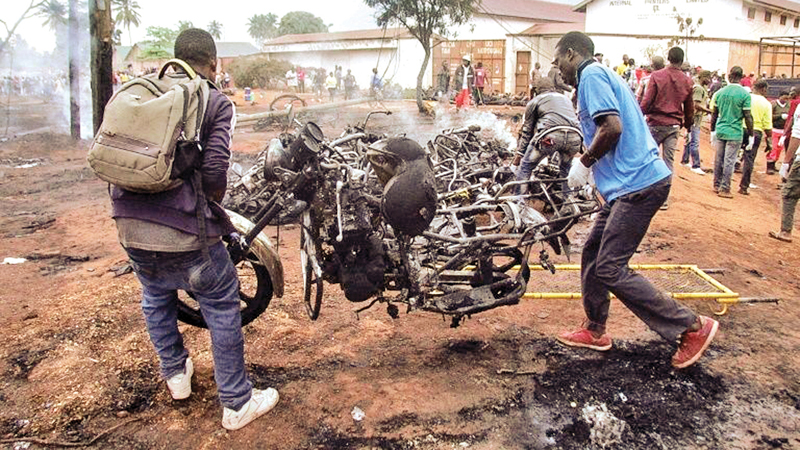 Two men carry the remains of a burnt out motorbike after a fuel tanker exploded in Tanzania.