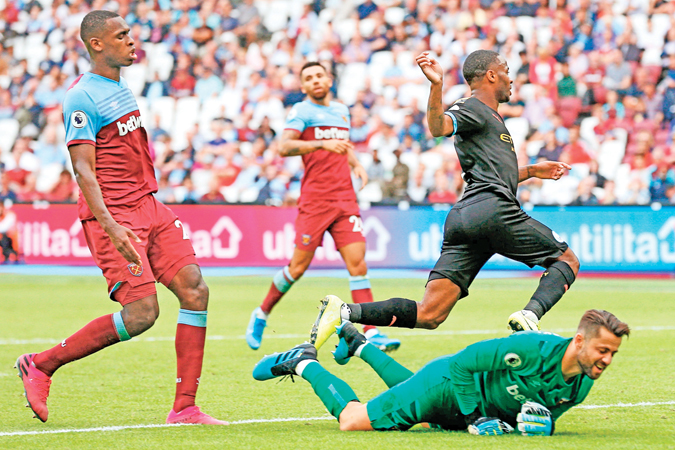 Manchester City's English midfielder Raheem Sterling (R) leaps over West Ham United's Polish goalkeeper Lukasz Fabianski (floor) as he scores their fifth goal and complete his hattrick during the English Premier League football match between West Ham United and Manchester City at The London Stadium, in east London on August 10.