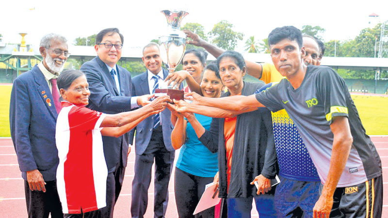 The Colombo Veteran athletes receiving the Overall Champion title from Malaysian High Commissioner Pan Yang Thai. The President of Sri Lanka Masters Athletics Neil Wickramaarachchi (extreme left) and Sri Lanka Masters Athletics Immediate Past President Tissa Samarasinghe are also present. (Pic by Ranjith Asanka)