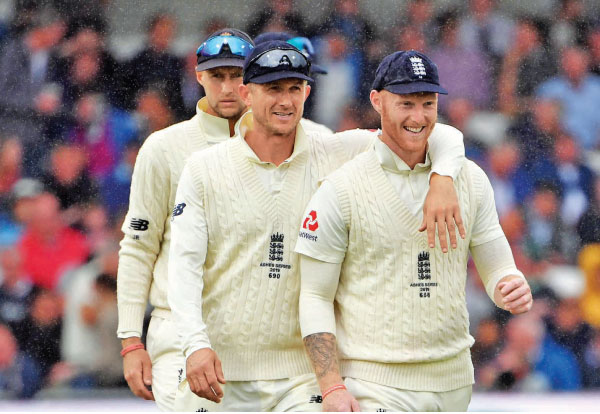 England's captain Joe Root (L), Joe Denly (C), and Ben Stokes (R) walk off the pitch due to rain during the first day of the third Ashes cricket Test match between England and Australia at Headingley in Leeds, northern England, on Thursday. - AFP