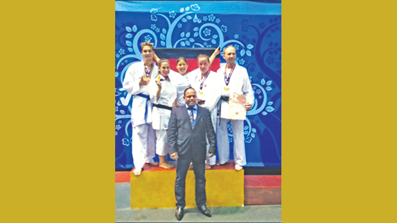 The Germany karate team (from left) Philipp Klemm, Ebru Baytemur, Corinna Reiter, Juliane Stube, and Andre Lassen celebrate on the podium with their Sri Lankan mentor Athula Minithanthri.