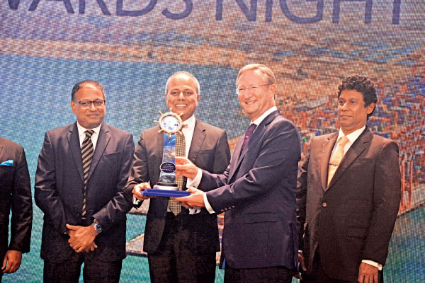Top official from Xpress Feeders who won the best feeder line award, receives the award from Minister Sagala Ratnayake. Chairman, Sri Lanka Ports Authority, Kavan Ratnayaka looks on. Picture by Sudath Malaweera