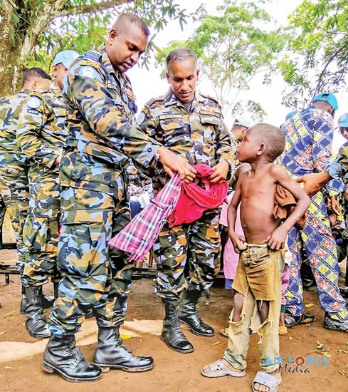 A child receiving clothes from a SLAF officer.