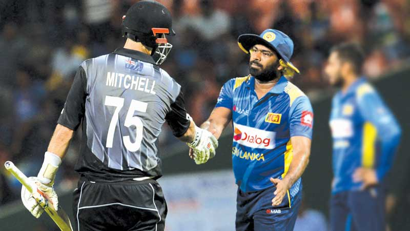 New Zealand's Daryl Mitchell (L) is congratulated by Sri Lanka's T20 cricket captain Lasith Malinga after victory in the first T20I at the Pallekele International Stadium on Sunday. – AFP