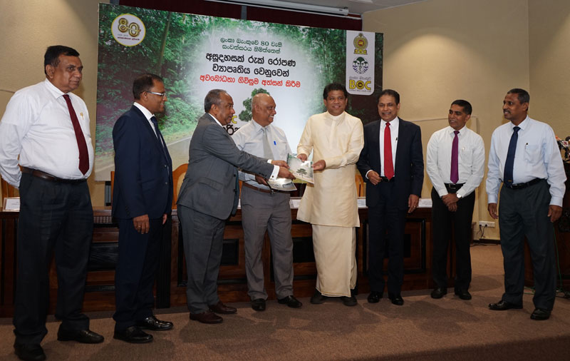 State Minister of Mahaweli Development and Environment Ministry Ajith Mannapperuma, Bank of Ceylon's Chairman, Ronald C. Perera exchanges the MoU. Other officials look on.