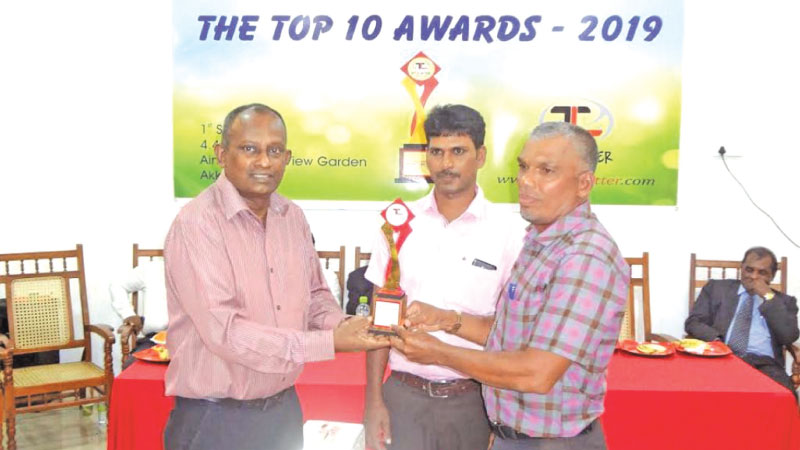 Ampara District Athletic Coach S.L. Thajudeen receiving a memento from Sammanthurai Electorate UNP Chief Organizer M.A.Hassan Ali during the event.