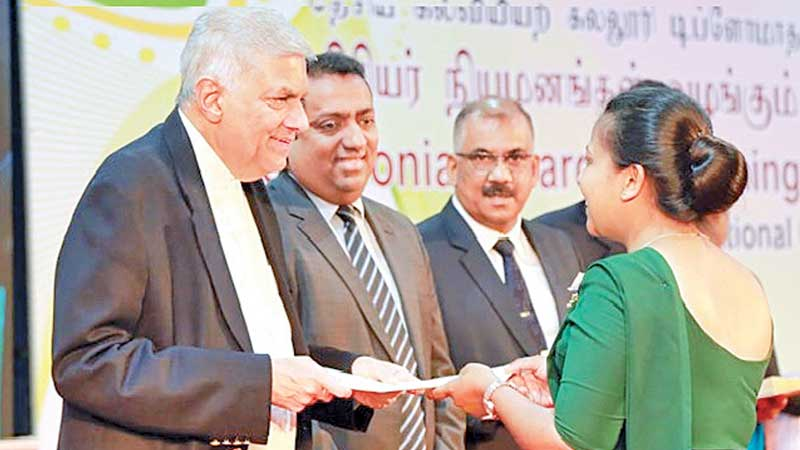 Prime Minister Ranil Wickremesinghe presenting the appointment letter to one of the teachers at Temple Trees yesterday.