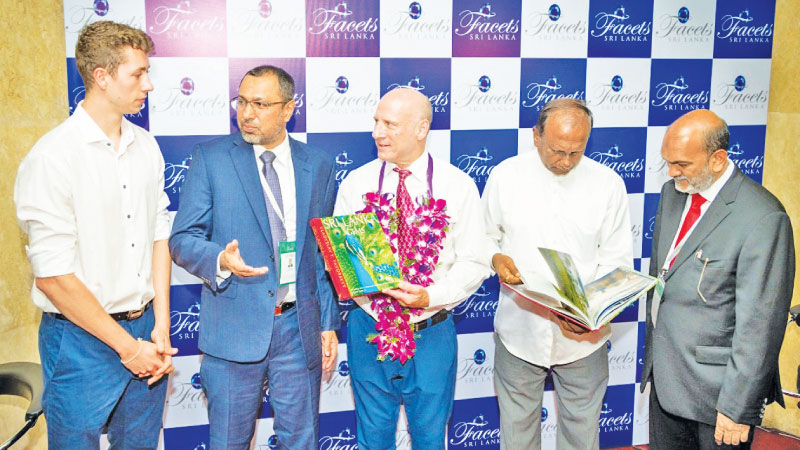 Sumithlal Mendis, Chairman, National Gem and Jewellery Authority, exibits a souvenir to Ahsan Refai, Chairman, Sri Lanka Gem and Jewellery Association at the 29th edition of Facets Gem and Jewellery Exhibition. Jason Allen, Altaf Iqbal and Guest of Honour Lewis Allen look on.