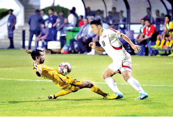 A Sri Lankan defender tries to stop a DPR Korea player from making an advance during the 2022 FIFA World Cup Qualifiers match played at Race Course International stadium yesterday. (Pic by Sulochana Gamage)