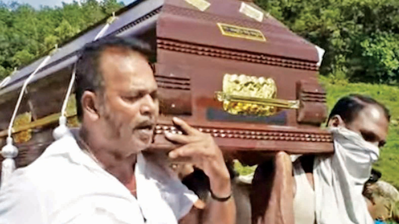 Deputy Minister Palitha Thevarapperuma carrying the corpse.