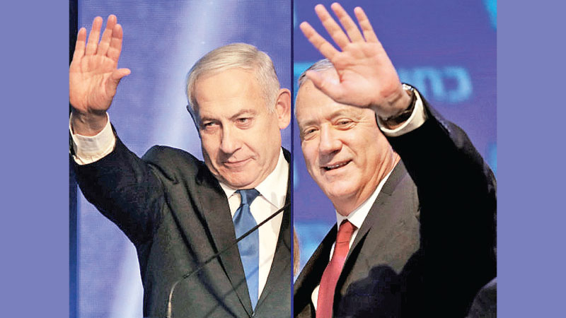 Benny Gantz (R), leader and candidate of the Israel Resilience party that is part of the Blue and White (Kahol Lavan) political alliance and Israeli Prime Minister Benjamin Netanyahu waving to supporters in Tel Aviv on Wednesday. - AFP