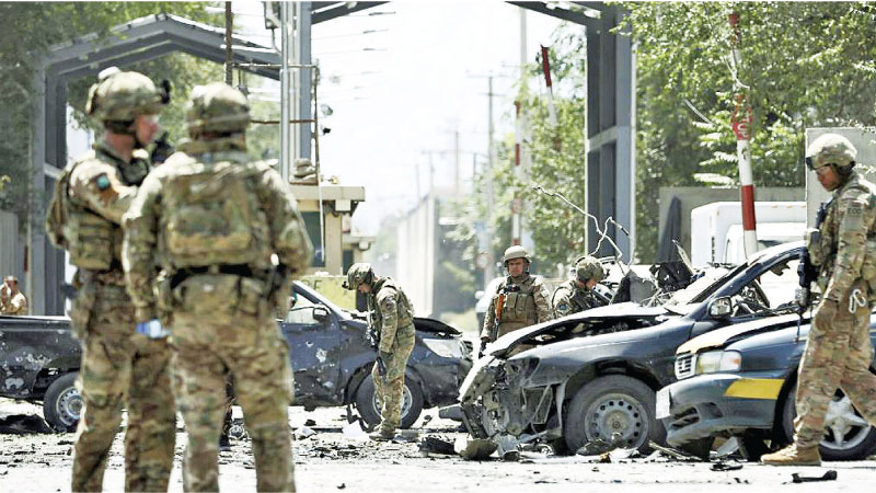 Afghan Security Forces personnel gather near the scene of the car bomb blast.