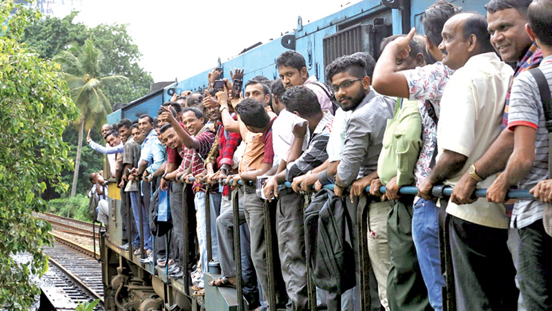 Passengers cling onto the train engine of an office train that operated during the strike yesterday. Picture by Sulochana Gamage.