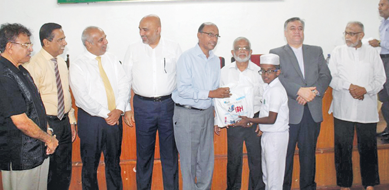 A child is presented with schoolbooks as Minister Rauff Hakeem, Iranian Ambassador Zaeri Amirani, Palestinian Ambassador Zuhair Mohammad Hamdallah Zaid and other officials look on.