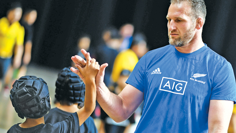 New Zealand's back row and captain Kieran Read gives a high fives to children at an All Blacks fan event in Beppu on Tuesday during the Japan 2019 Rugby World Cup. - AFP