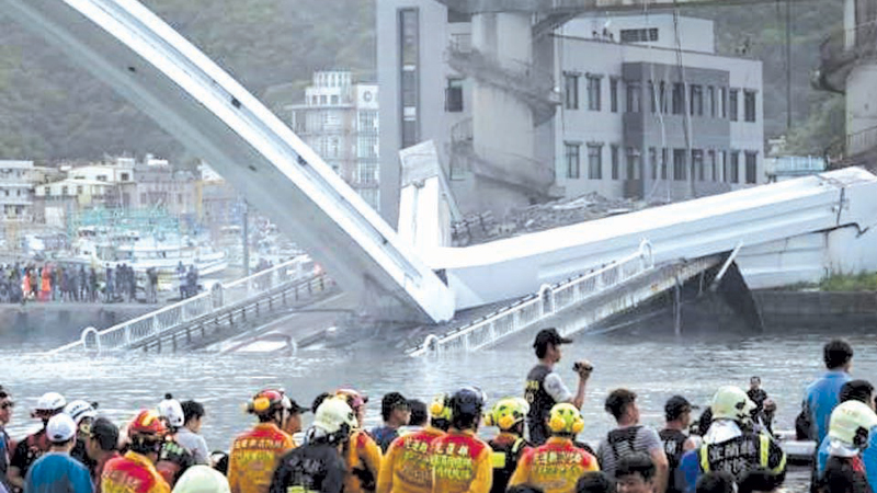 People in the northeastern town of Nanfangao look at the collapsed bridge.