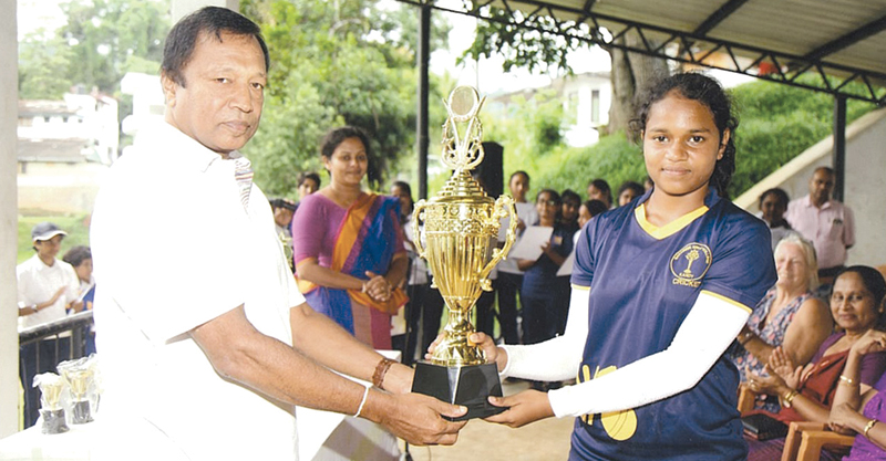 Sayuni Premaratne, captain of the winning team receiving the Withanachchi Trophy from  the husband of Indra Withanachchi.