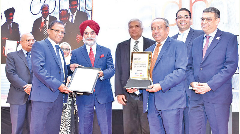 "Prime Minister Wickremesinghe and the Indian High Commissioner Taranjit Singh Sandhu presenting the Award ""Top Ten Most Admired Company in Sri Lanka"" to the Bank's Chairman, President's Counsel Ronald C. Perera and the CEO/ General Manager Senarath Bandara"