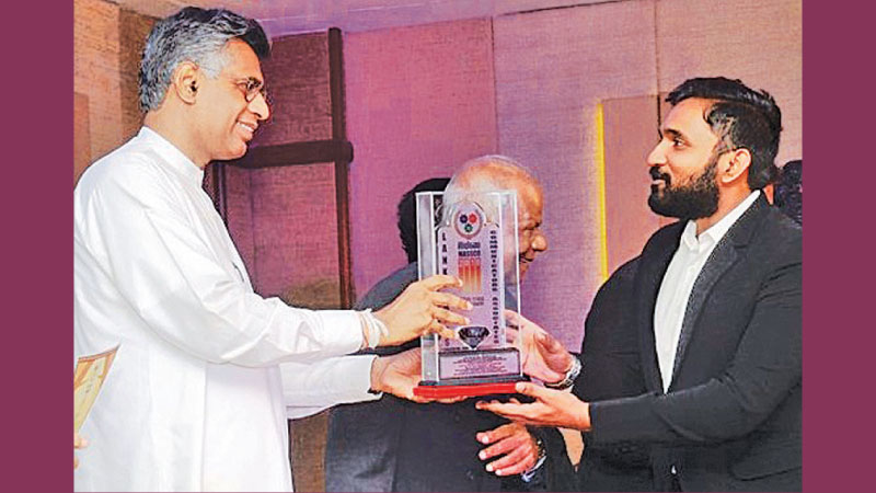 Thineth Jayasundara receives the award from Minister Patali Champika Ranawaka