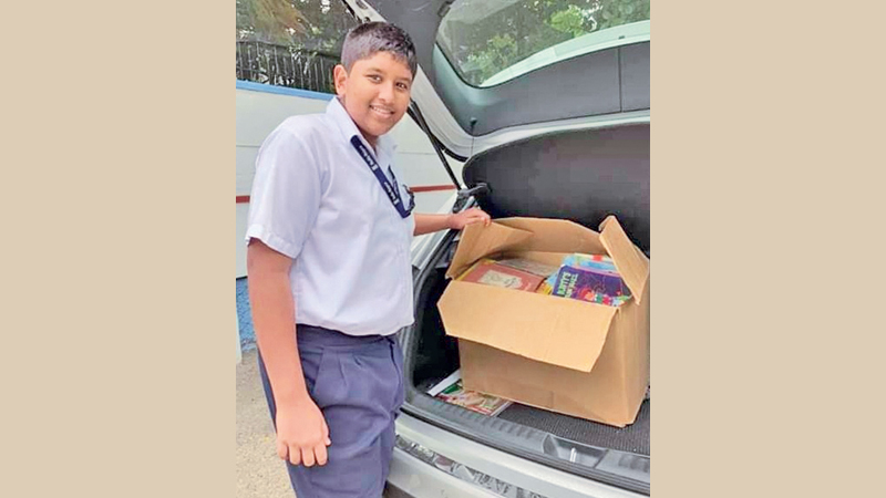 Rishen Rajapaksa unloads some of the books for the Meewellewa Vidyalaya library.