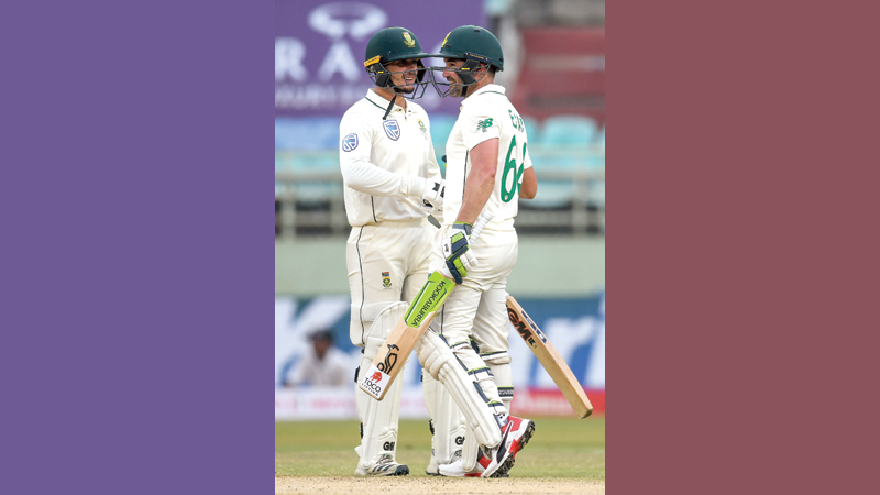 South Africa's Quinton de Kock (L) greets his teamate Dean Elgar after scoring 150 runs during the third day's play of the first Test match against India at the Dr. Y.S. Rajasekhara Reddy ACA-VDCA Cricket Stadium in Visakhapatnam yesterday. - AFP