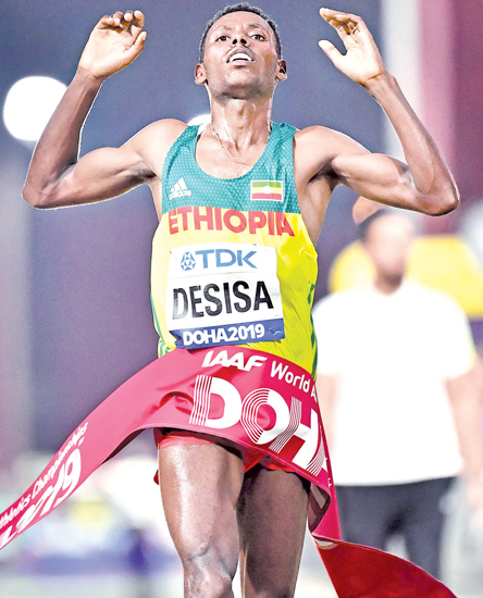Ethiopia's Lelisa Desisa celebrates as he crosses the finish line and wins the Men's Marathon at the 2019 IAAF Athletics World Championships in Doha on Sunday. - AFP