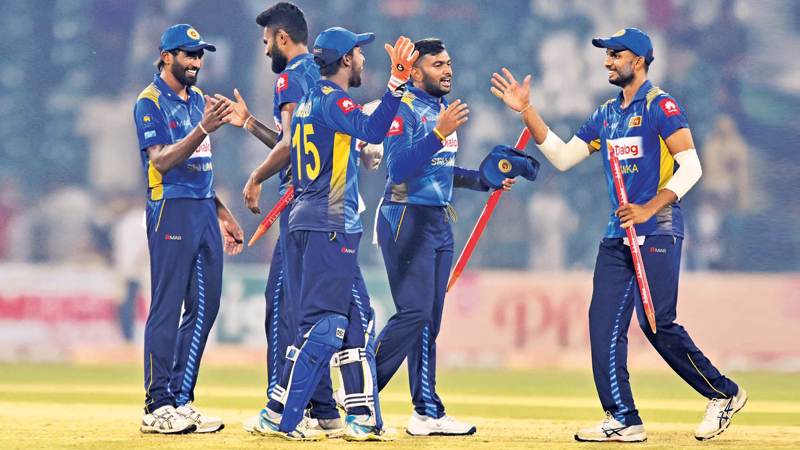 Sri Lanka's cricketers celebrate victory in the first Twenty20 International cricket match against Pakistan at the Gaddafi stadium in Lahore on Saturday. – AFP