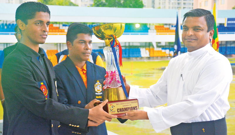 The First XI Captain of S. Thomas' College R.H. Rambukpotha(left) and St. Peter's skipper R.G.S. Sandaruwan Kaveeshwara receiving the trophy as joint champions from St. Peter's College Rector Father Rohitha Rodrigo.  Picture by Ranjith Asanka