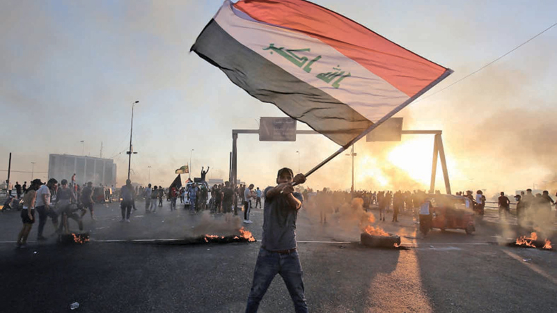 An Iraqi protester waves the national flag during a demonstration against state corruption, failing public services, and unemployment, in Baghdad on October 5.