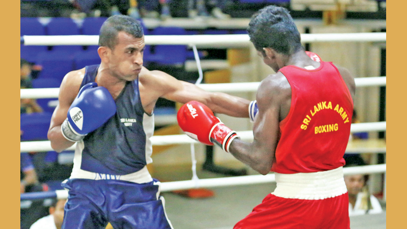 Navy's Gayan Indika Bandara (blue) lands a left jab to the body of Army's Raveendranath in a Fly weight bout at the BASL Clifford Cup Boxing Championship at the Royal MAS Arena on Monday. Pictures by Sulochana Gamage
