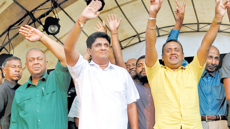 RALLYING THE  DEEP SOUTH:  Seven SLFP members and one JVP member of the Kamburupitiya Pradeshiya Sabha expressed support to NDF Presidential candidate Sajith Premadasa at an election rally held in Kamburupitiya town yesterday.   Picture shows Minister Sajith Premadasa and the PS members waving to the crowd. Finance Minister Mangala Samaraweera was also present. by Hirantha Gunathilake