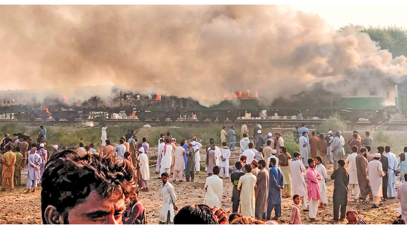 Residents gather beside the burnt-out train carriages after a passenger train caught on fire near Rahim Yar Khan in Punjab province yesterday. - AFP