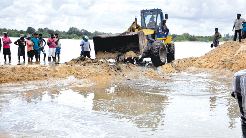 Removing sand to release flooded water.