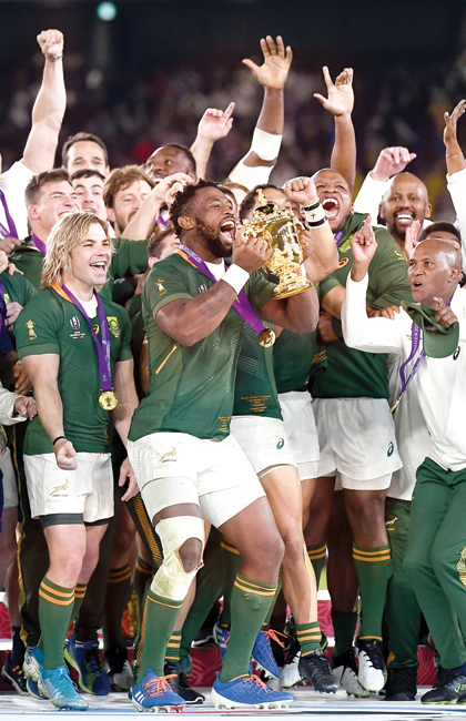 South Africa's flanker Siya Kolisi (C) lifts the Webb Ellis Cup as they celebrate winning the Japan 2019 Rugby World Cup final match between England and South Africa at the International Stadium Yokohama in Yokohama on November 2,