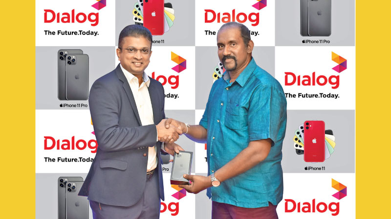 Dr. Siriwardena, the first iPhone 11 Pro Max customer receives the device from Supun Weerasinghe, Group Chief Executive, Dialog Axiata PLC.