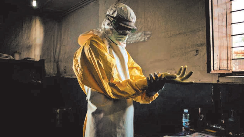 A health worker puts on his personal protective equipment before entering the red zone of a MSF (Doctors Without Borders) supported Ebola Treatment Centre (ETC), where he will check up on patients on November 6, 2018 in Bunia, Democratic Republic of the Congo.
