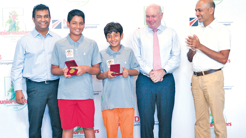 School Team Event winners Reshan Algama  and Kvahn Tejwani (Center Left and Center Right) from Colombo International School with the chief guest Dr John Scarth, Principal of The British School in Colombo (Right), Prabodha Samarasekera, CEO of NDB Wealth Management (Far Left) and Chandana Weerasinghe, SLG's Junior Sub Committee Member (Far Right).