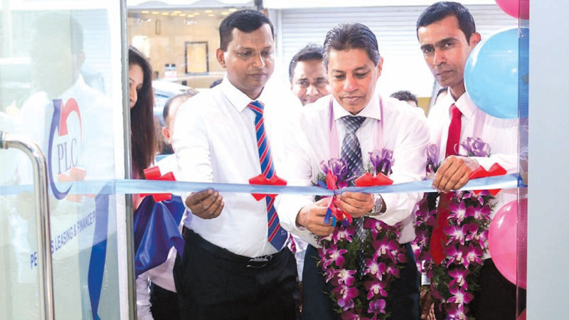Sabry Ibrahim, CEO and GM, PLC at the inauguration of the relocated People's Leasing Negombo Service Centre.  Lionel Fernando Senior DGM and Nalin de Silva Senior Manager- People's Leasing Negombo.