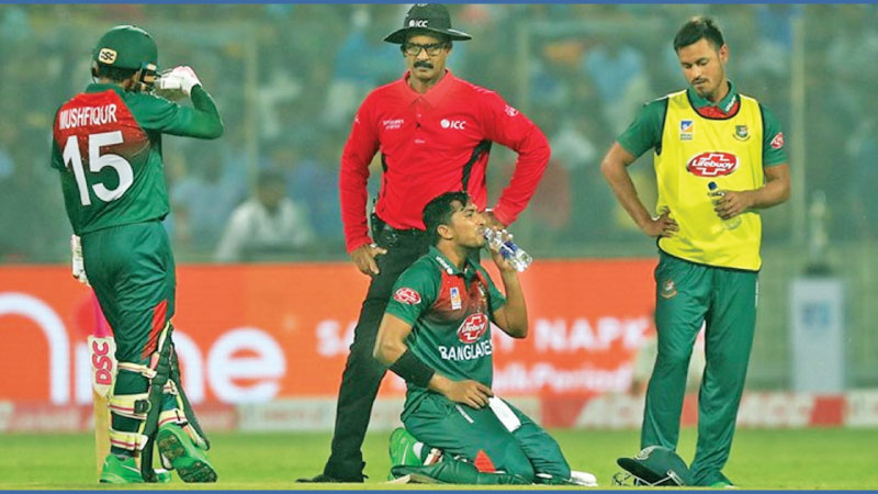 Bangladesh batsman Soumya Sarkar (right) refreshes himself after vomiting on the field during the first T20I against India at Delhi.