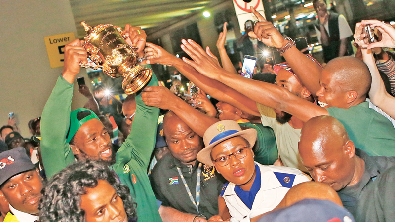 Supporters reach to try and touch the Web Ellis Cup carried by Springboks captain Siya Kolisi (L) through the crowd upon the team's arrival at the O.R. Tambo International Airport in Johannesburg on Tuesday. South Africa's World Cup winning rugby squad arrived home to a heroes' welcome and will be embarking on a nationwide Champions tour. – AFP
