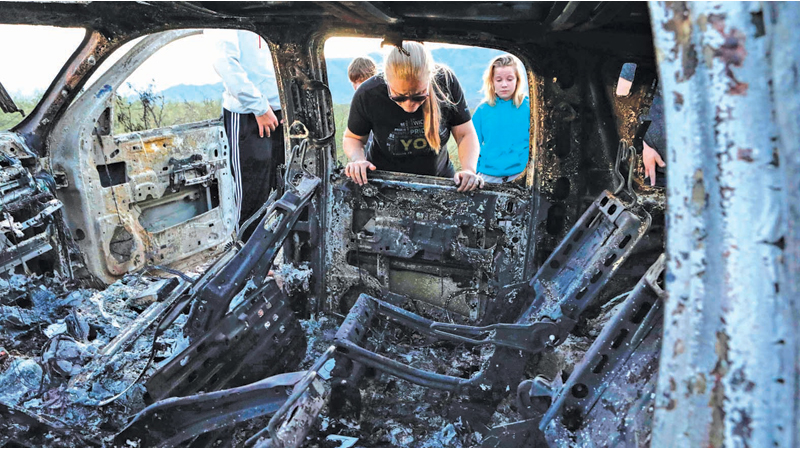 Members of the Lebaron family observe the wreckage of the burned out vehicle where nine members of a family were killed and burned during an ambush at Bavispe, Sonora mountains, Mexico on Tuesday. - AFP