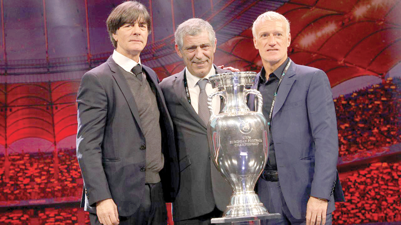 Germany coach Joachim Loew, Portugal coach Fernando Santos and France coach Didier Deschamps pose with the trophy after being drawn in group E.