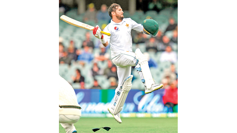 Pakistan batsman Yasir Shah celebrates scoring his century against Australia on the third day of the second cricket Test match in Adelaide on Sunday. AFP