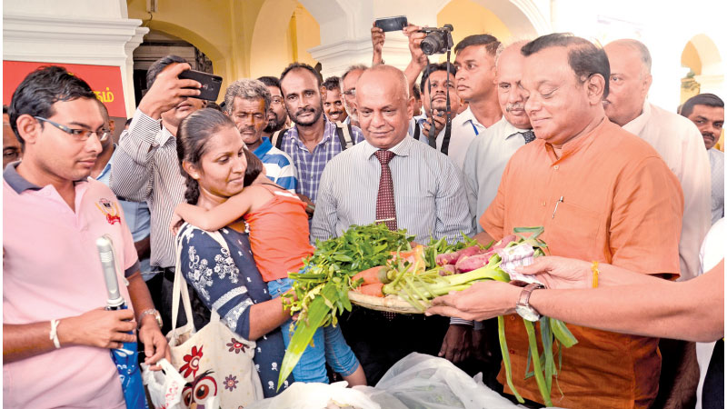 Railway Services State Minister C. B. Rathnayake distributing the vegetables yesterday at the Maradana Railway Station. Picture by Wimal Karunathileke