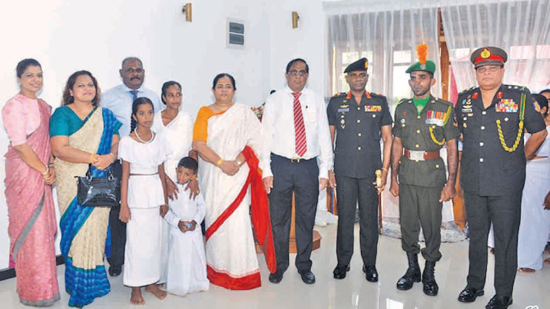 The recipient of the house constructed by Ariya with members of the management and Sri Lanka Army