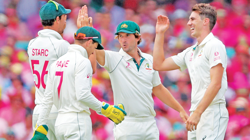 Australia's Pat Cummins (R) celebrates after dismissing New Zealand's Tom Latham during the third day of the third cricket Test match between Australia and New Zealand at the Sydney Cricket Ground in Sydney on January 5.