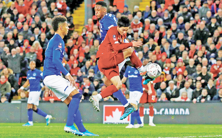 Liverpool's Takumi Minamino in action with Everton's Yerry Mina and Mason Holgate.