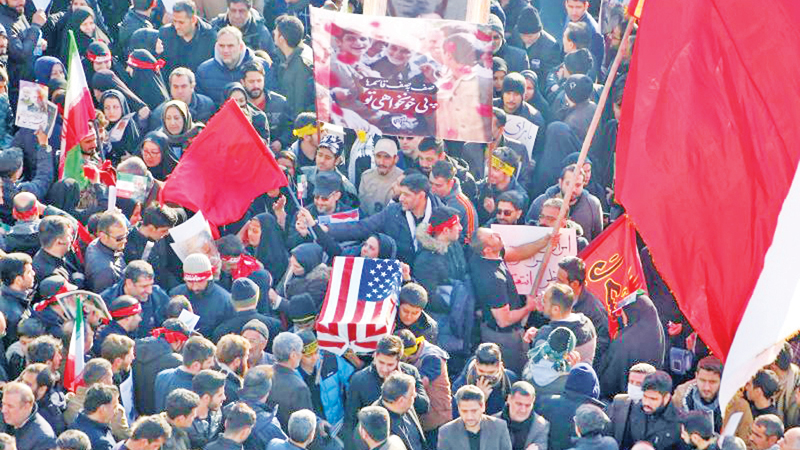 Iranian mourners carry a symbolic coffin wrapped in a US flag during the funeral procession of General Qasem Soleimani in the capital Tehran on January 6, 2020. - AFP